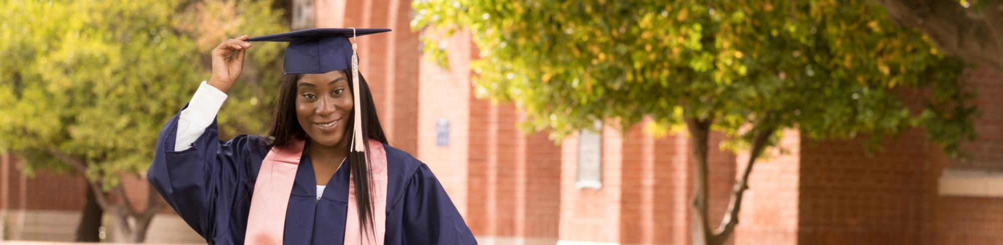 Headshot of a student in regalia as they smile towards the camera holding their cap