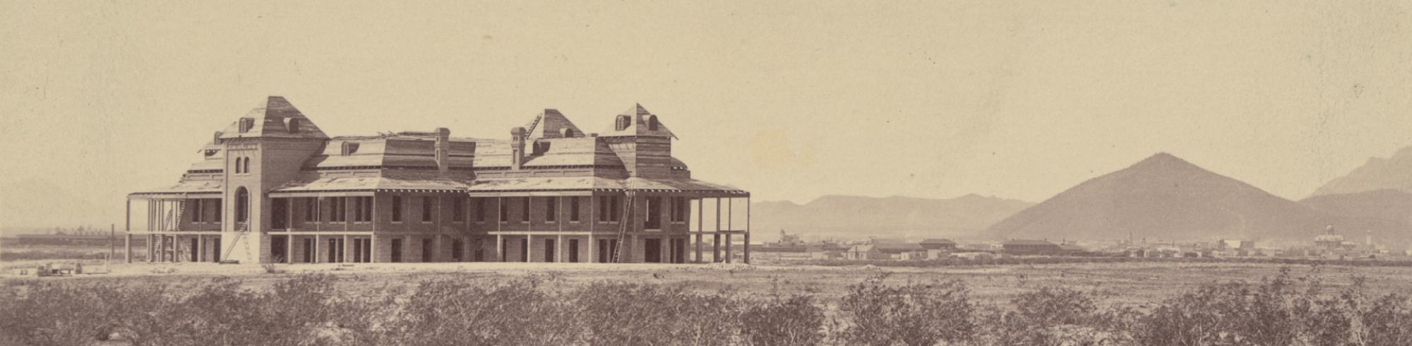 Old Main against a desert backdrop as it's being built, mountains can be seen in the background