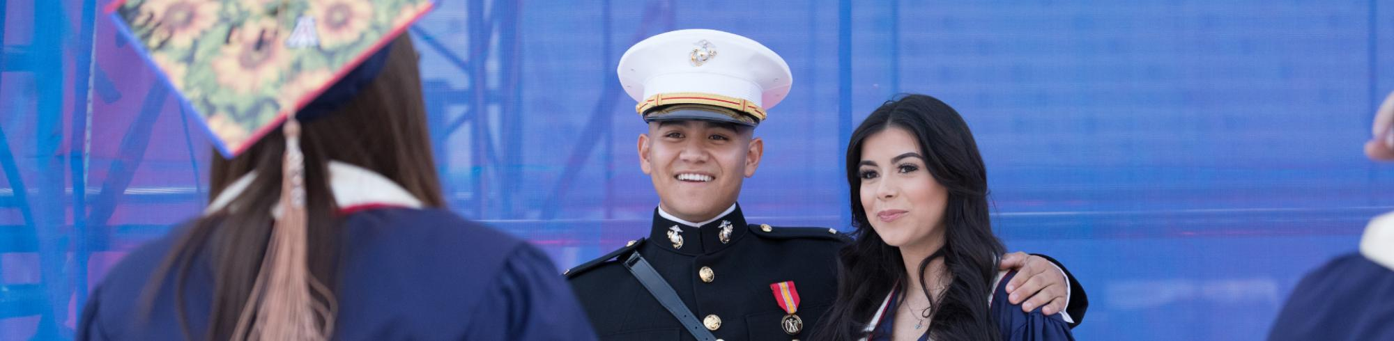 A graduating veteran poses with another graduate in regalia at Commencement as they get ready to take a photo