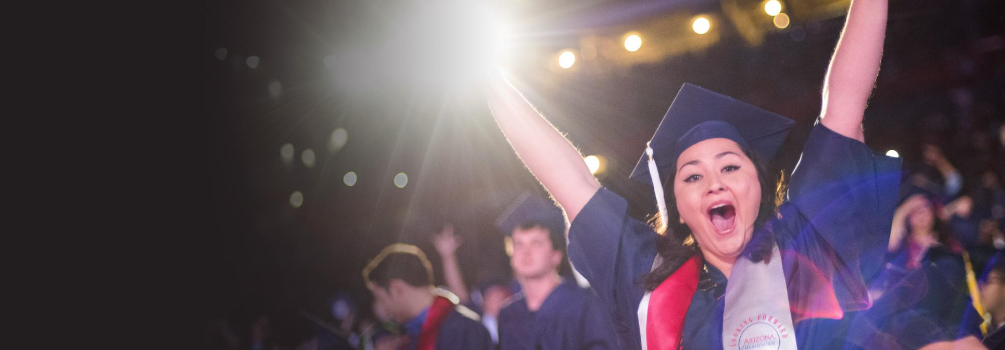 A graduate stands and raises their arms in excitement and joy