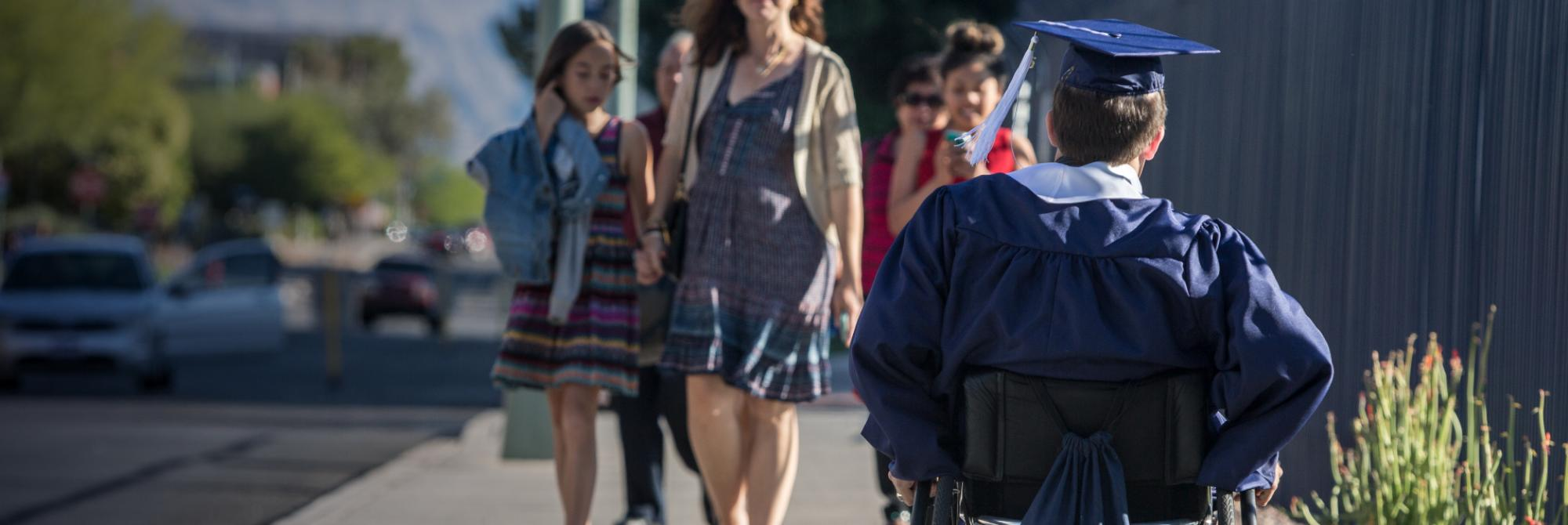 A student in a wheelchair heads to Arizona Stadium, the student is facing away from the camera as he heads to Commencement