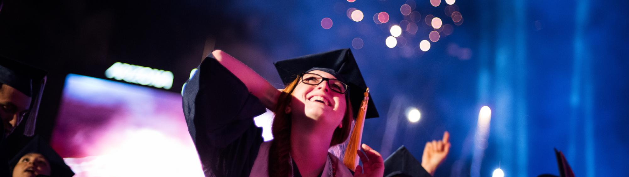 A student smiles and looks up towards the sky as fireworks shoot up following the end of the Commencement Ceremony