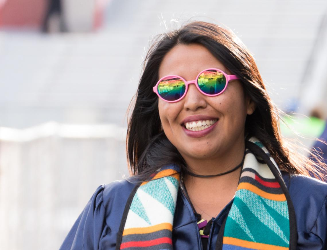 Photo of a student smiling towards the camera and she gets ready to celebrate Commencement