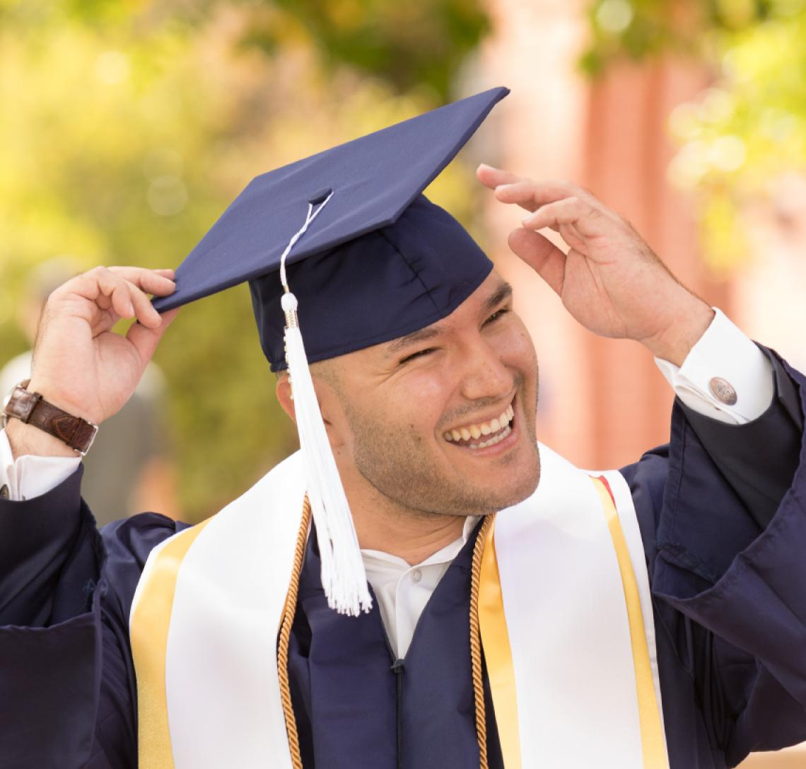 Photo of a student smiling as he adjusts his graduation cap