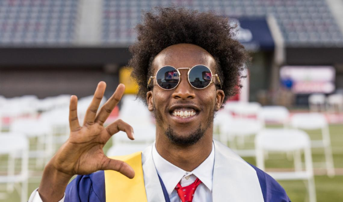 Graduating student in regalia looking towards the camera as they make the Wildcat hand sign