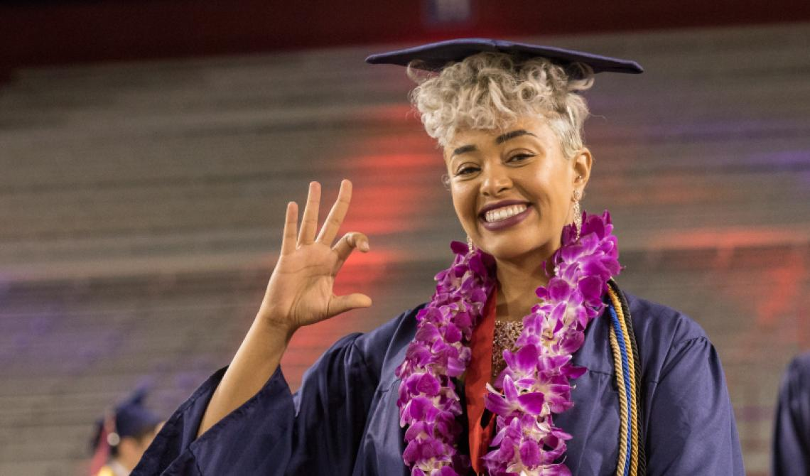 A student in full regalia makes the Wildcat symbol with her hand and smiles at the camera
