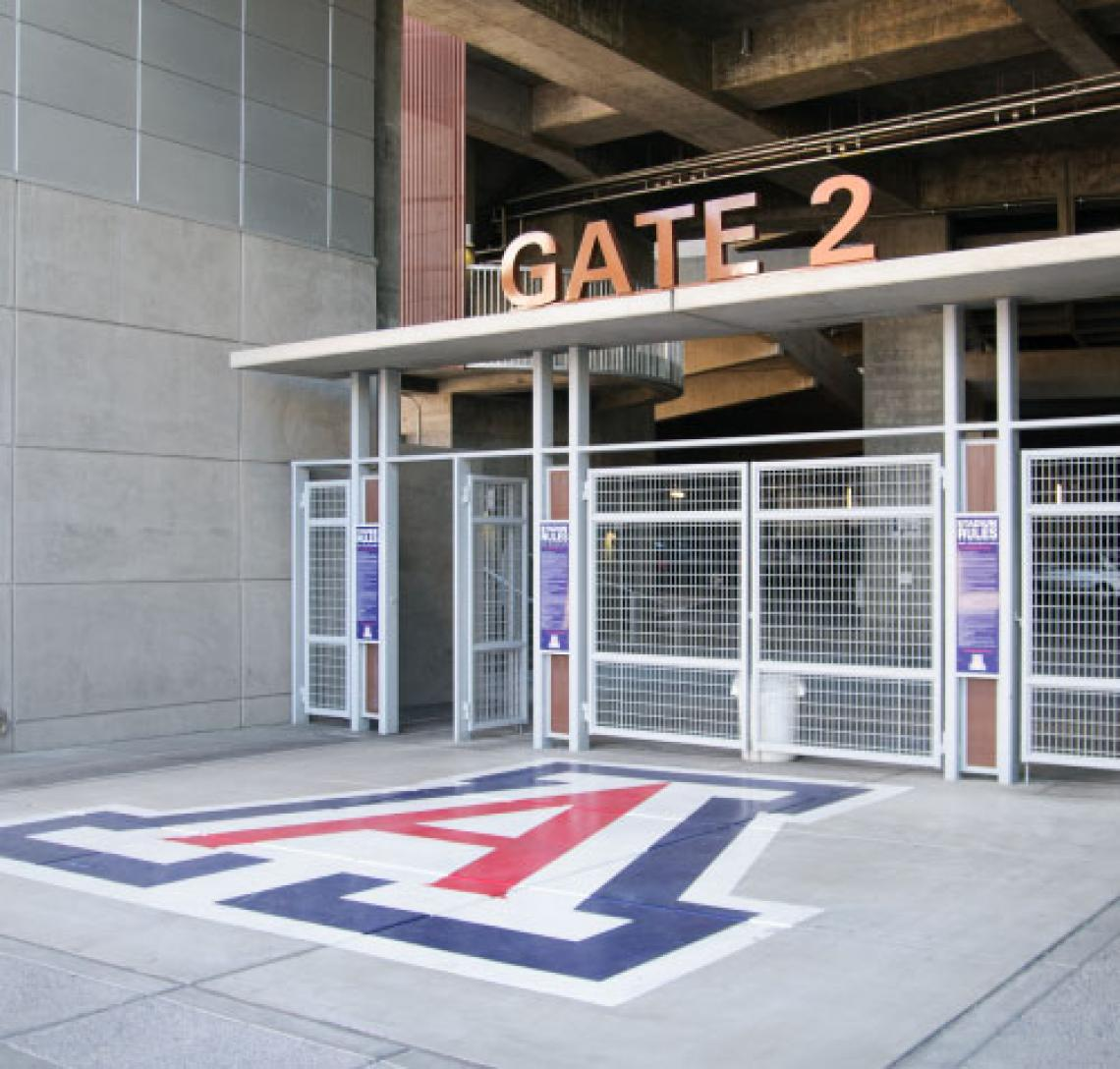 """An entrance into Arizona Stadium with words reading """"Gate 2"""" overhead can be seen with the Block A painted onto the floor in front of the gate"""
