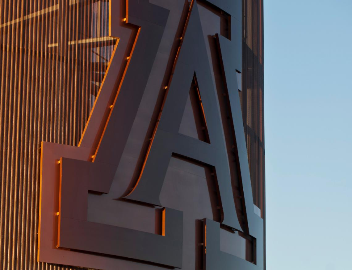 Photo of a close-up shot of the Block A atop Arizona Stadium against a blue sunset sky