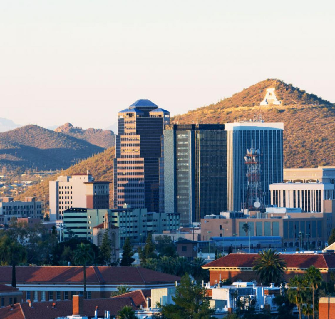 A photo of the City of Tucson skyline as seen from a distance with A Mountain in the background
